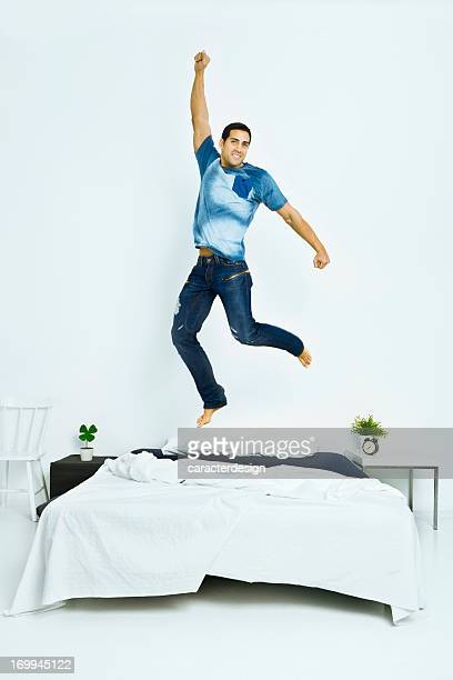 Happy man jumping on bed