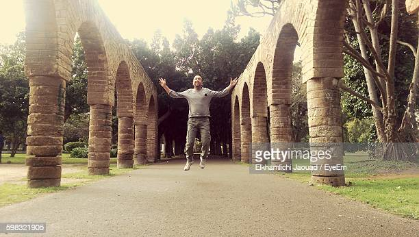 Happy Man Jumping On Street Amidst Colonnade
