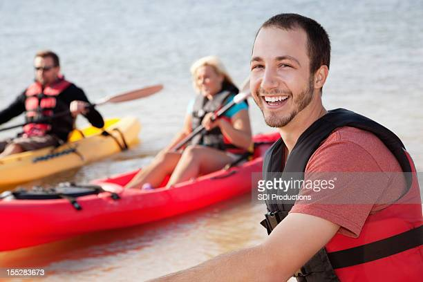 Happy man kayaking with his friends