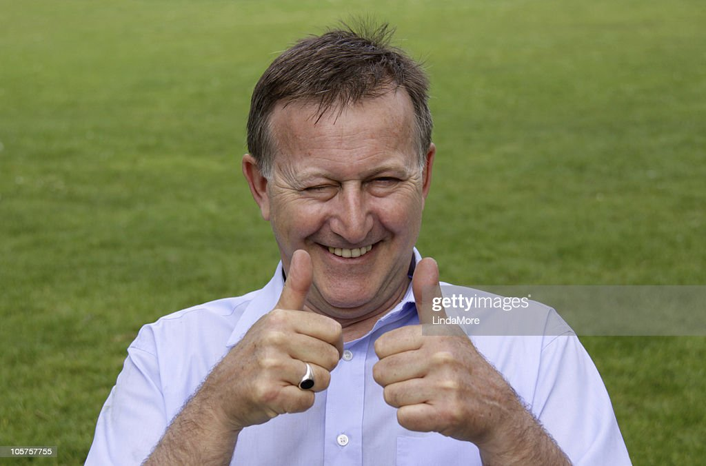 Happy man laughing with thumbs up, outdoors : Stock Photo