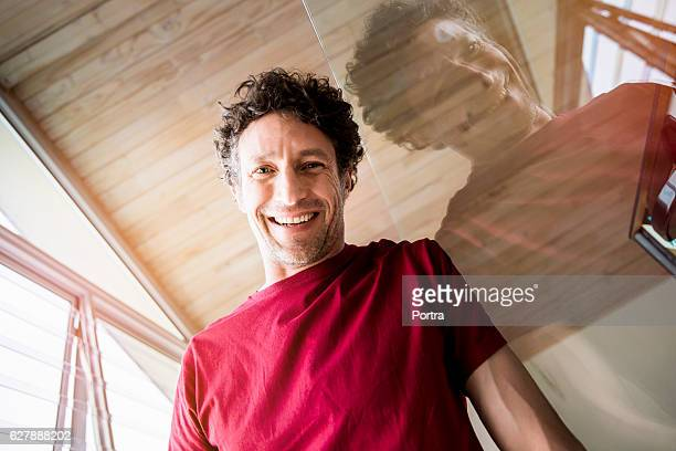 Happy man leaning on glass wall at home