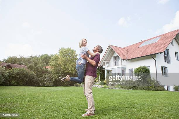 Happy man lifting up woman in garden