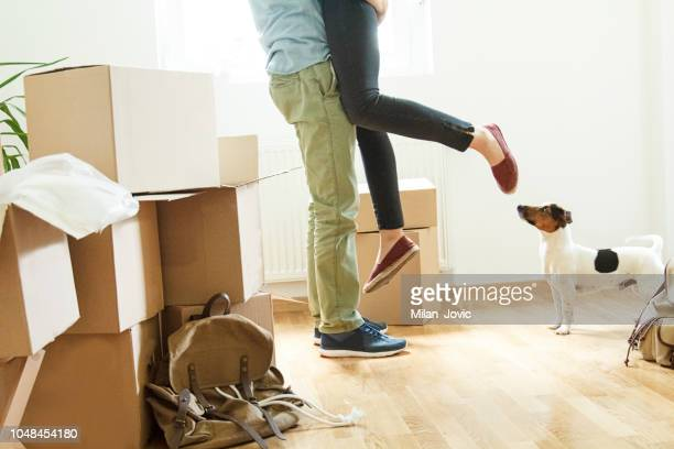 Happy man lifting woman in new house