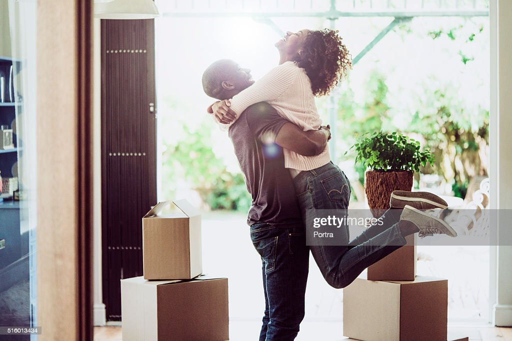 Happy man lifting woman in new house : Stock Photo