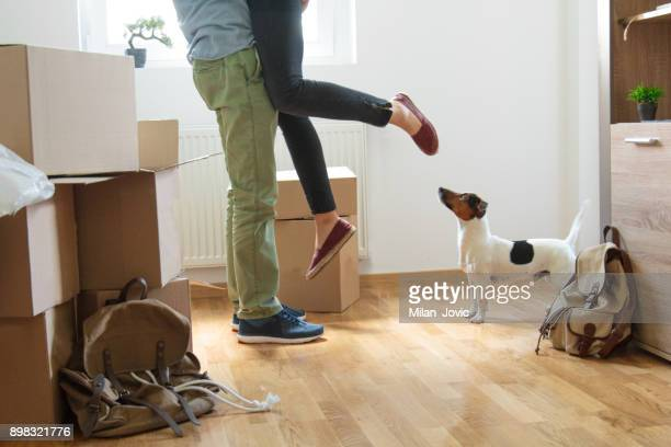 happy man lifting woman in new house - young couple stock pictures, royalty-free photos & images
