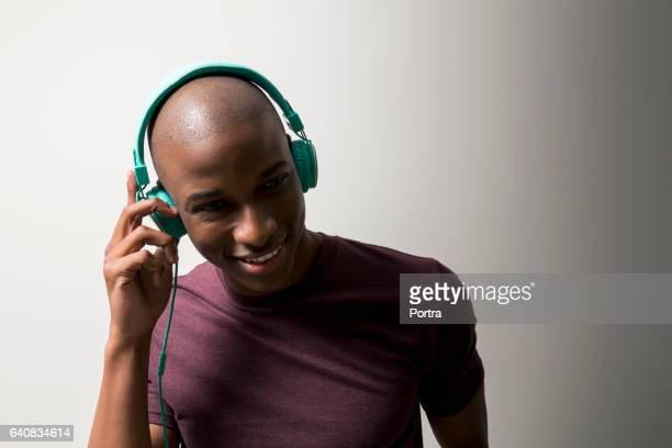 Happy man listening music against white background