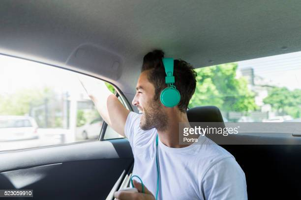 Happy man listening to music on headphones in car