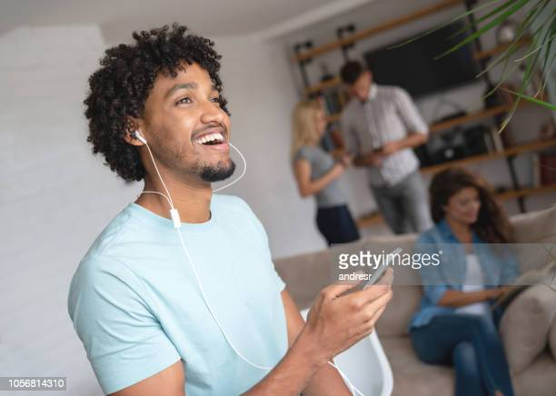 Happy man listening to music with headphones at home