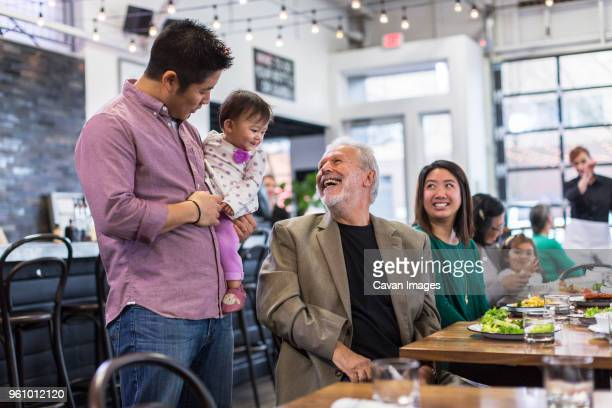 Happy man looking at baby girl being carried by father in restaurant