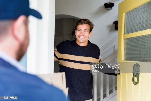 happy man looking at delivery person at doorway - receiving stock pictures, royalty-free photos & images