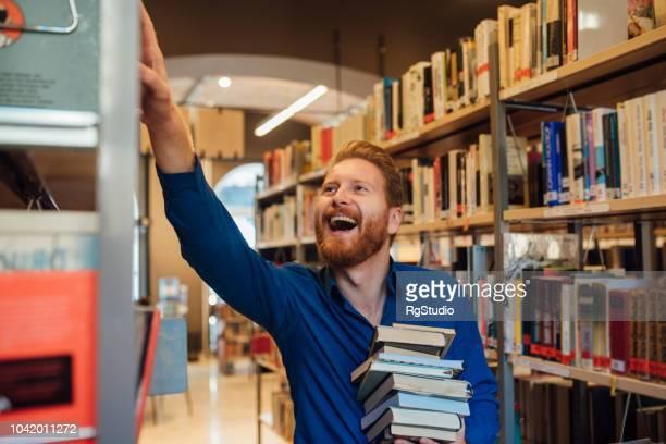 glücklicher mann, blick auf das bücherregal - bibliothekar stock-fotos und bilder