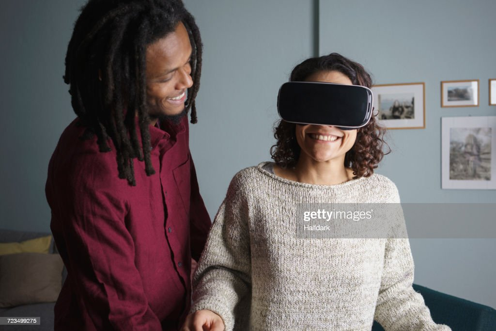 Happy man looking at woman using virtual reality headset in living room