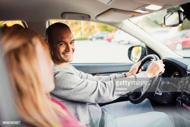 happy man looking at woman while sitting in electric car - electric car fotografías e imágenes de stock
