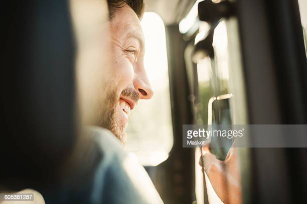 Happy man looking away while photographing through smart phone in car