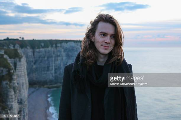 Happy Man Looking Away While Standing On Cliff Against Sea During Sunset