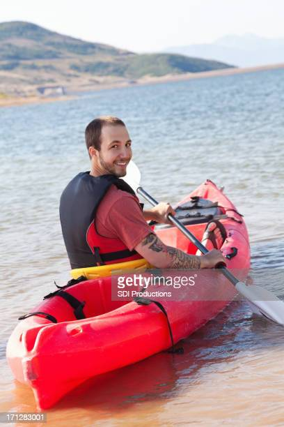 Happy man looking back while kayaking