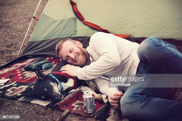 Happy man lying on dog outside tent at camp site
