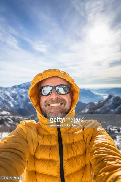 happy man on mountain snowy with down jacket smiling at camera - switzerland stock pictures, royalty-free photos & images