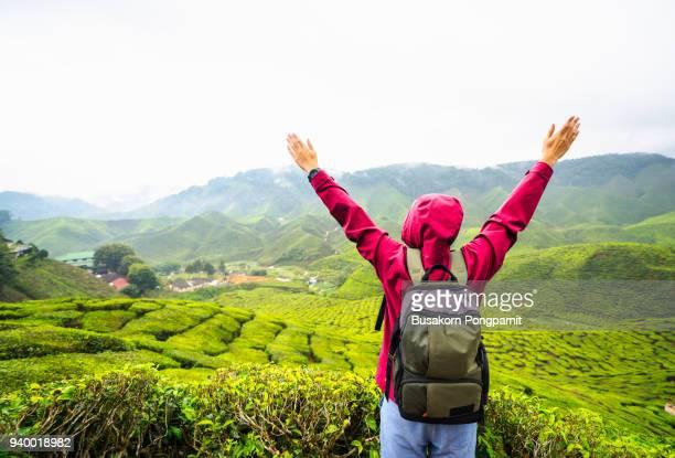 Happy Man on mountain summit enjoying freedom