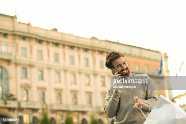 Happy man on the phone after shopping.