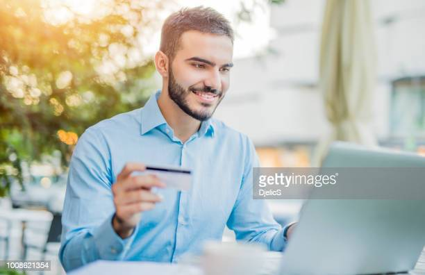 happy man paying online. - bank account stock pictures, royalty-free photos & images