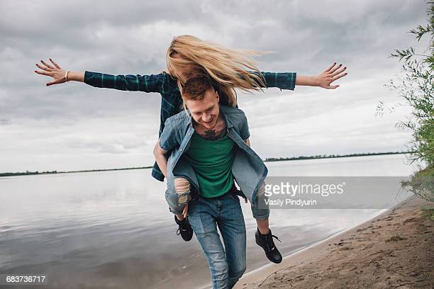 Happy man piggybacking girlfriend on lakeshore against sky