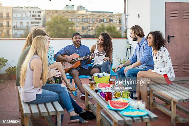 Happy man playing guitar for friends on terrace