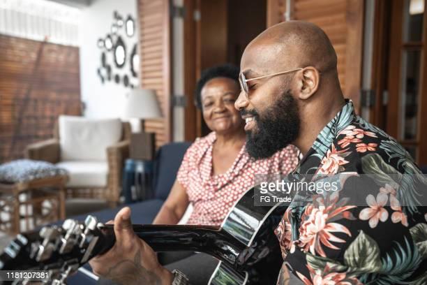 homem feliz que joga a guitarra a sua matriz - músico - fotografias e filmes do acervo