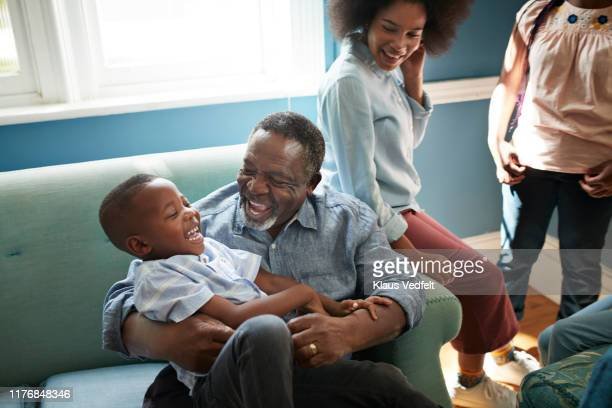happy man playing with boy on sofa at home - teenager alter stock-fotos und bilder
