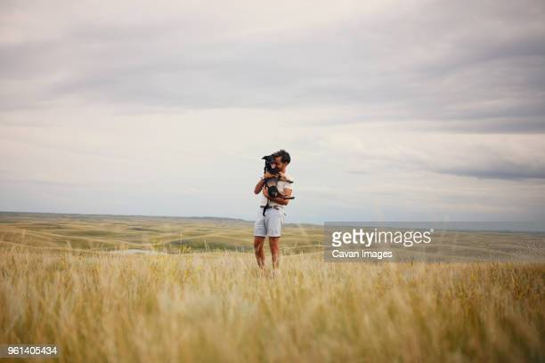 happy man playing with dog on grassy field against cloudy sky - saskatchewan stock pictures, royalty-free photos & images