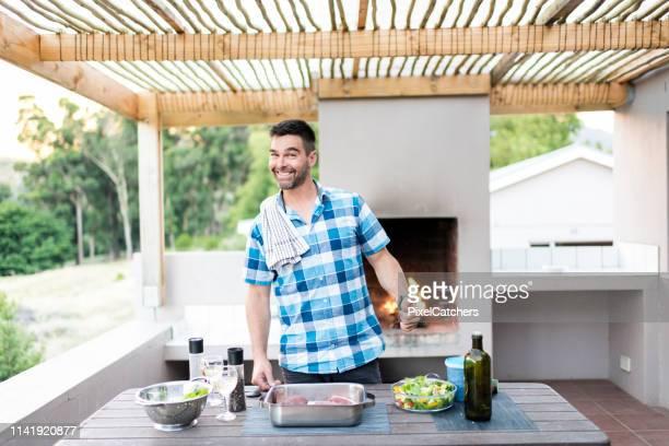 homem feliz que prepara a carne para um bbq - só um homem - fotografias e filmes do acervo