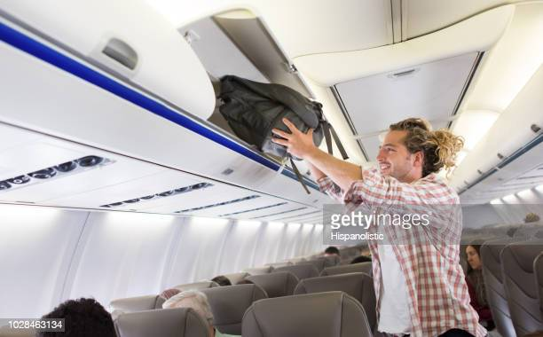 Happy man putting his carry-on luggage in the overhead compartment