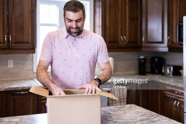happy man receiving and opening a packgage at home - unboxing stock pictures, royalty-free photos & images