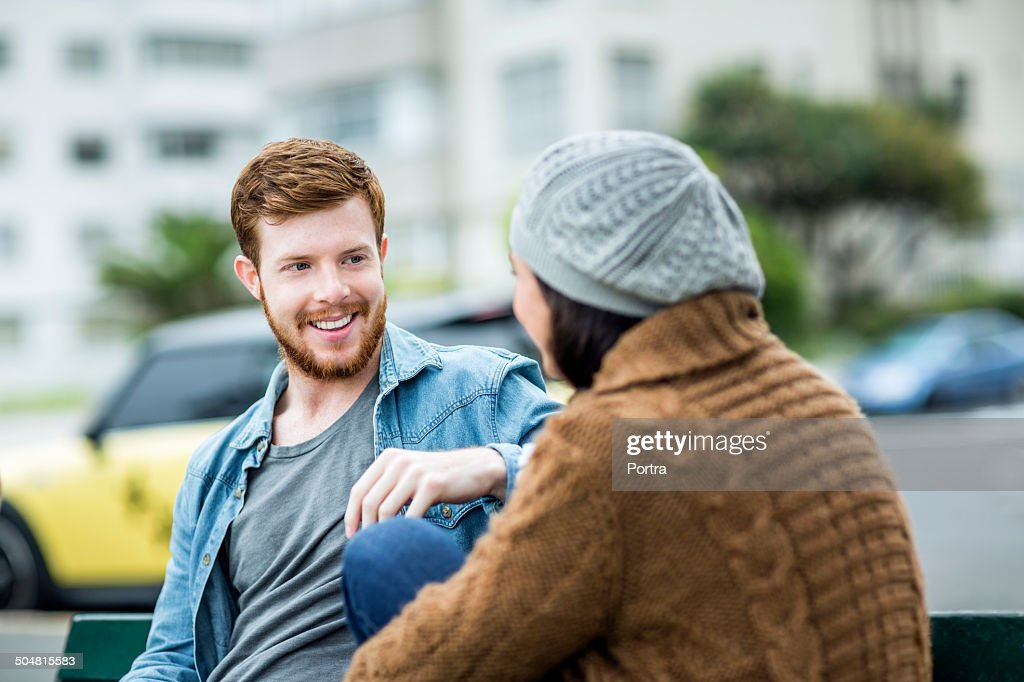 Happy man relaxing with woman on park bench : Stock Photo