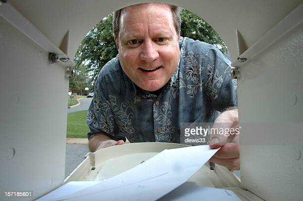 happy man removes letter from the mailbox - send stock pictures, royalty-free photos & images