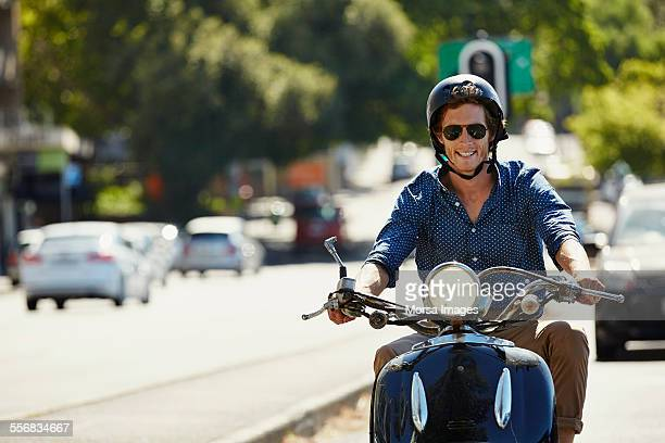 happy man riding motorcycle on sunny day - mid volwassen mannen stockfoto's en -beelden