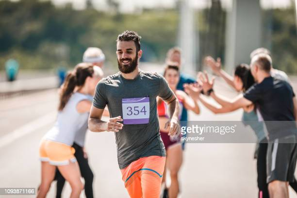 happy man running a marathon race on the road. - half_marathon stock pictures, royalty-free photos & images