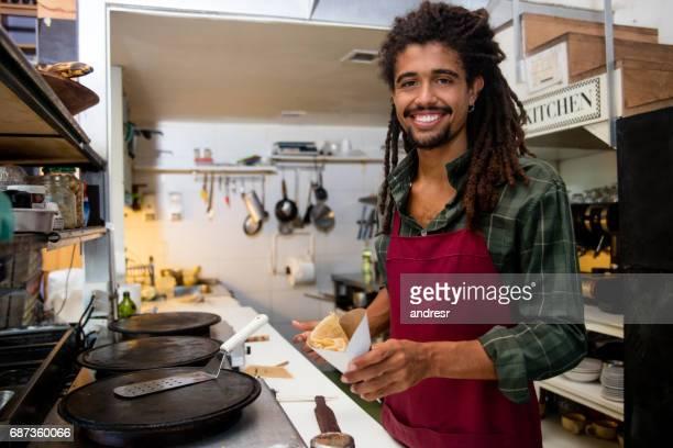 Happy man serving crepes at a restaurant
