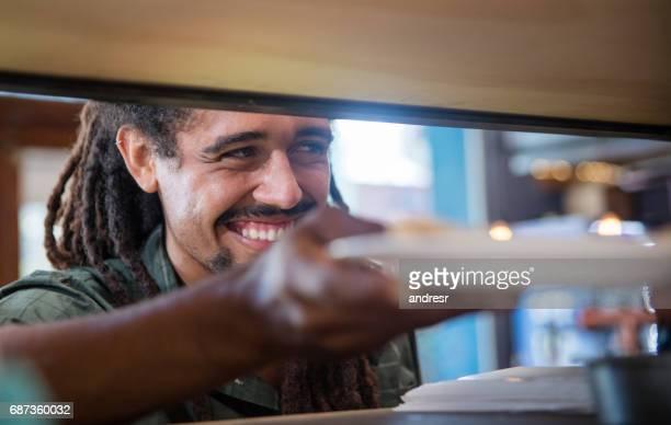 Happy man serving food at a restaurant
