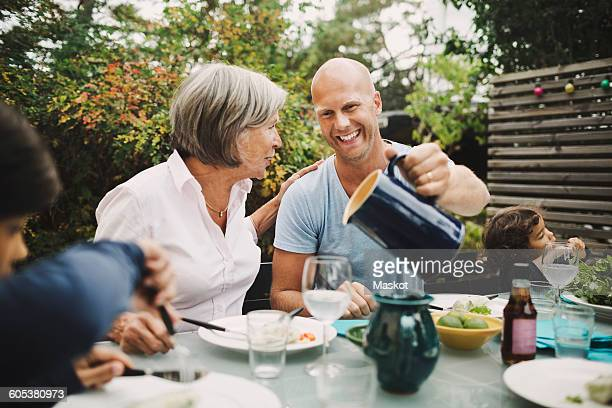 happy man serving water to mother at outdoor dining table - four people stock pictures, royalty-free photos & images
