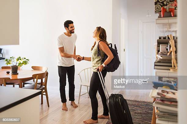 Happy man shaking hand with woman going for vacation
