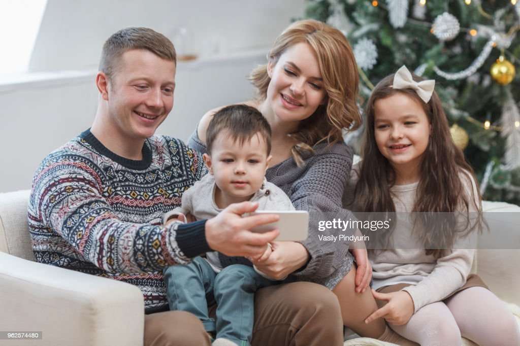 Happy man sharing mobile phone with family on sofa at home during Christmas : Stock Photo