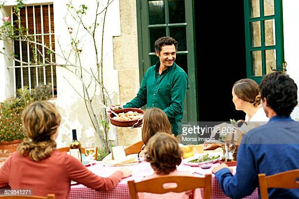 happy man showing dish to family at outdoor table - europa meridionale foto e immagini stock
