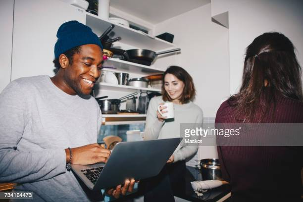 happy man showing laptop to female friend with coffee cup in kitchen - roommate stock pictures, royalty-free photos & images