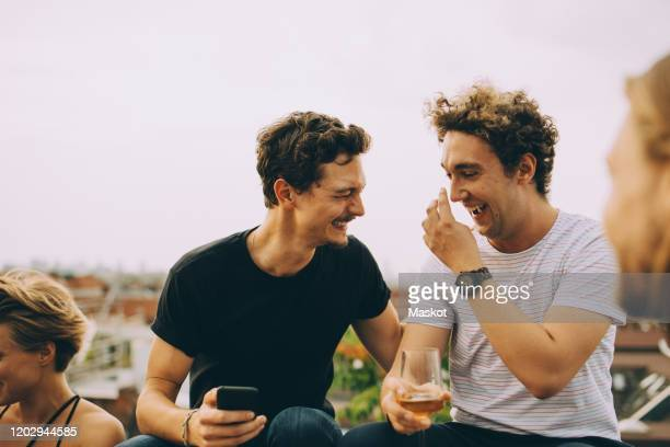 happy man showing mobile phone to friend having drink at terrace during party - men friends beer outside stock pictures, royalty-free photos & images