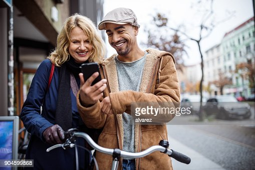 Happy man showing smart phone to friend