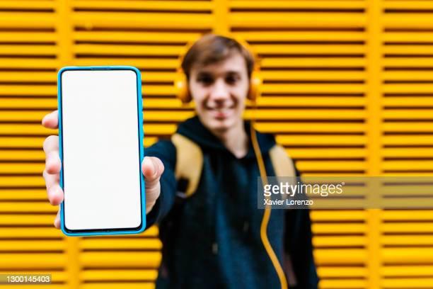 happy man showing smartphone screen outdoors - tonen stockfoto's en -beelden