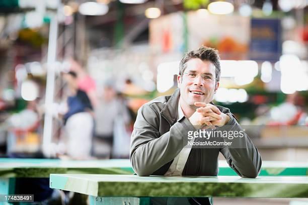 Happy man sitting at table in market fair horizontal