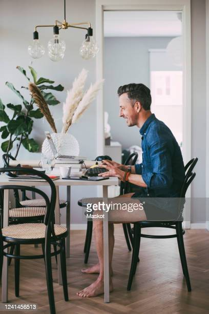 happy man sitting at table in underwear working at home having a video call - 在宅勤務 ストックフォトと画像