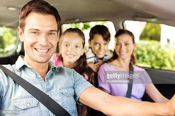 happy man sitting with family in car - family inside car stock photos and pictures